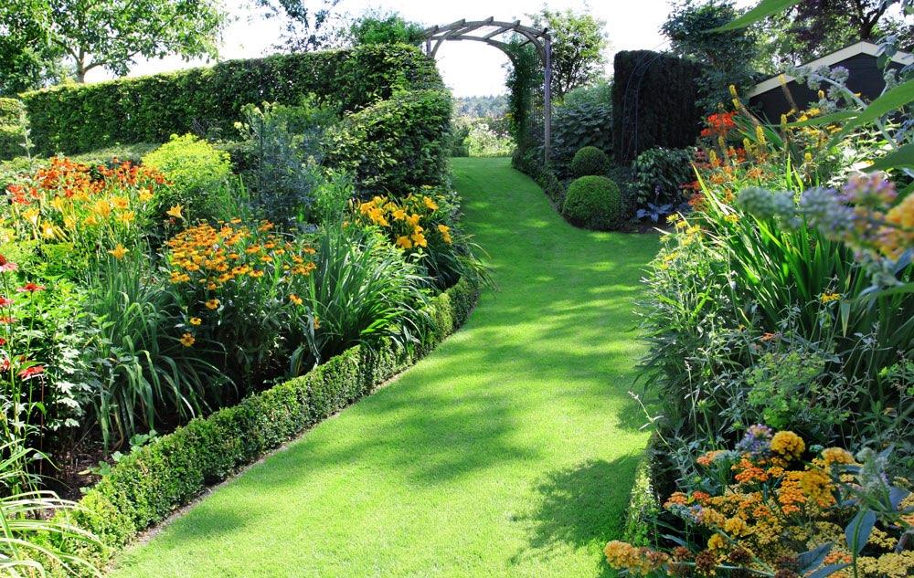 Bloementuin met een paadje van gras - Geplaveid voor allee tuin ...